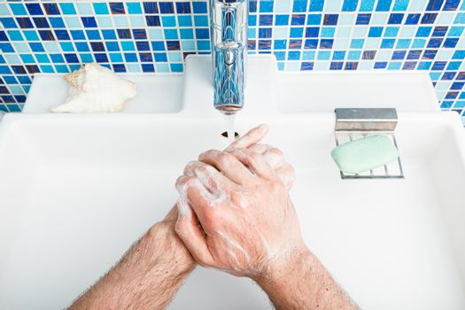 Man washing hands with soap and water performing basic protective measures against spreading of coronavirus epidemy