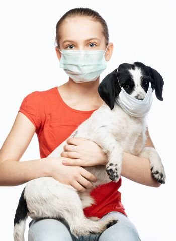 Portrait of child sitting with her dog both wearing protective surgical masks performing basic protective measures against transmission of coronavirus COVID-19 disease