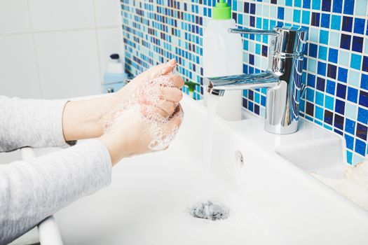 Child diligently washing hands with antibacterial soap and water performing basic protective measures against spreading of coronavirus COVID-19 desease