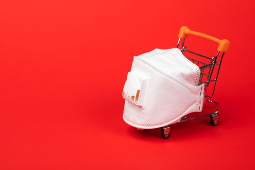 Supermarket cart with protective mask on on red background. Safe shopping during Coronavirus COVID-19 pandemic outbreak concept