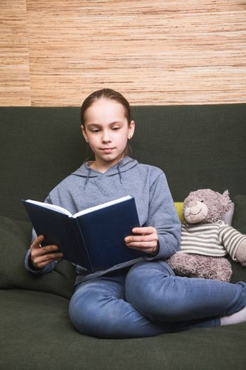 Schoolgirl reading a book sitting on a sofa with toy bear. Girl is studying at home doing her homework during self-isolation. Homeschooling concept