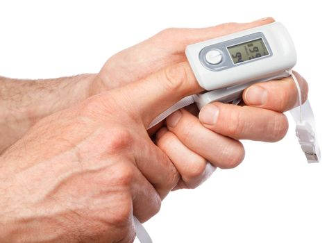 Close-up shot of person using finger pulse oximeter to check oxygen saturation and heart rate tracking coronavirus symptoms - epidemic virus outbreak concept