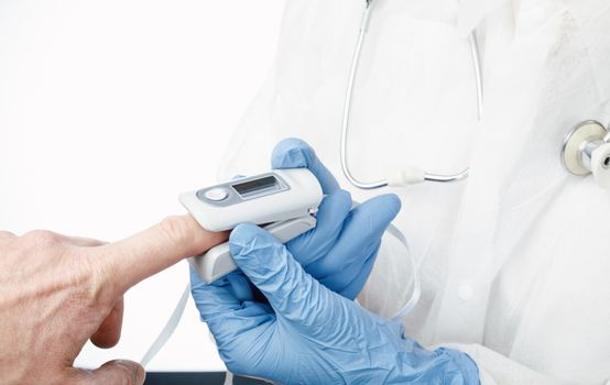 Close-up shot of doctor using finger pulse oximeter to check oxygen saturation and heart rate of a person tracking coronavirus symptoms - epidemic virus outbreak concept