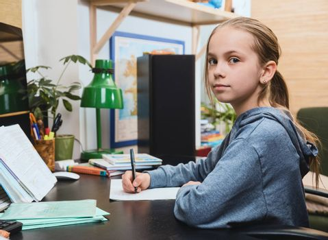 Schoolgirl writing in a notebook sitting by a table. Girl is studying at home doing her homework during self-isolation. Homeschooling concept