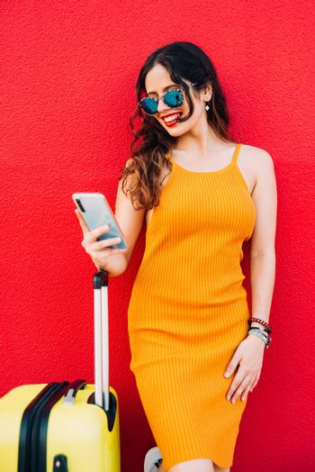 woman with a suitcase and smartphone waiting lean against a wall