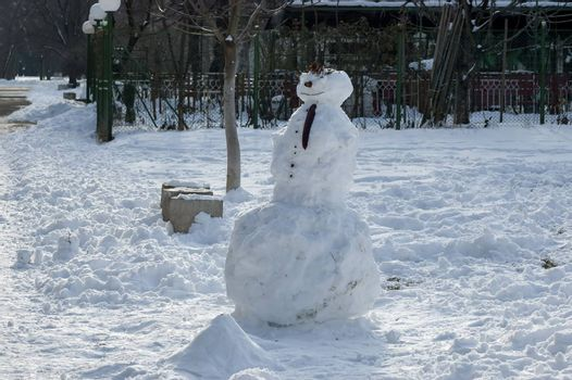 Winter scene with a snowman made with handy materials in the park, Sofia, Bulgaria