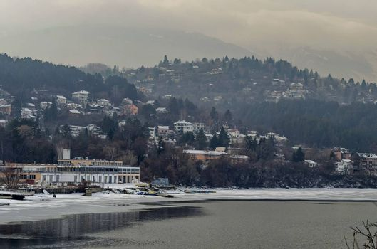 Winter scene with frozen lake, snowy mountain, glade, forest and residential district of bulgarian village Pancharevo, Sofia, Bulgaria
