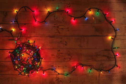 Christmas background with colorful lights and free text space. Christmas lights frame. Garland. Flat lay, top view, copy space.