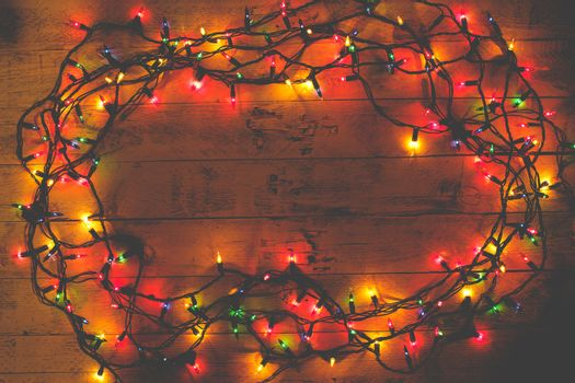 Christmas rustic background - vintage planked wood with lights and copy space. Garland. Tinted photo. Flat lay, top view.