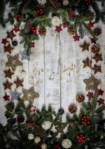 Christmas decoration composition. Frame made of fir branches, pinecones and berries on the wooden board in vintage style. Flat lay, top view, copy space.