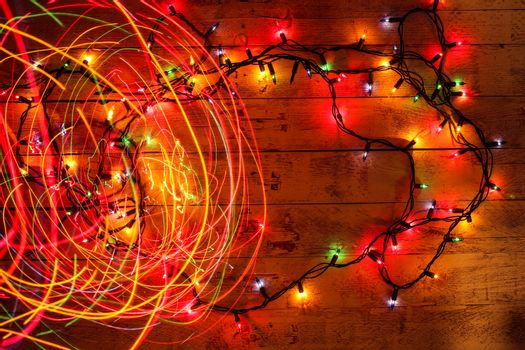 Colorful Christmas garland warm lights. Multicolored light lines. Wooden background. Long exposure. Top view. Horizontal shot. Copy space.