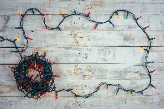 Christmas background with colorful lights and free text space. Garland lights frame on a wooden background. Flat lay, top view, copy space.