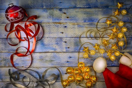 Christmas background. Top view of Christmas red ball, santa hat and christmas lights with ribbons on rustic vintage wooden background. Flat lay, copy space.