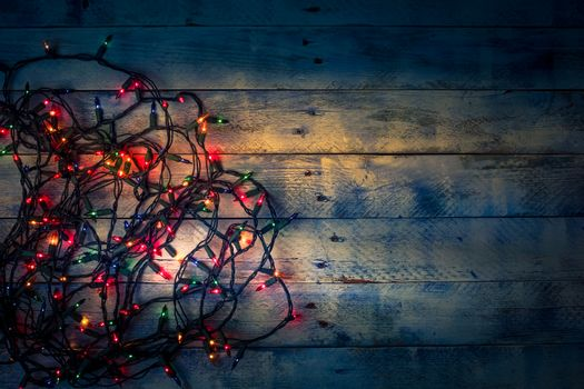 Christmas background with lights and free text space. Christmas lights garland. Flat lay, top view, copy space. Horizontal shot.
