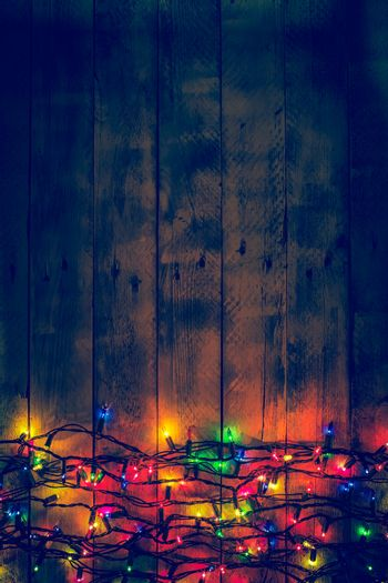 Colorful Christmas garland warm lights. Multicolored lights. Wooden background. Long exposure. Top view. Vertical shot. Copy space.