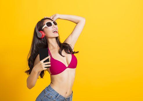 beautiful woman wearing swimsuit bikini and singing by mobile phone