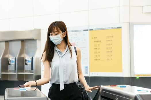 business Woman wear medical mask and hand scanning train ticket to subway entrance gate