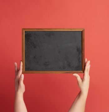 woman hands holds brown empty wooden frame on red background, place for an inscription
