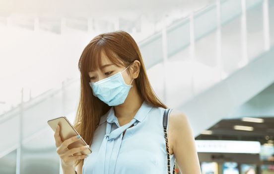 business woman wearing face mask at train station watching the mobile phone