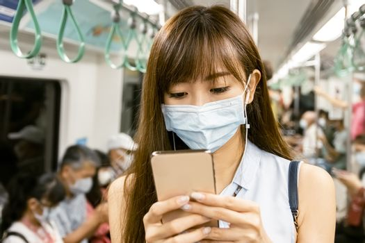 young Asian woman wearing  surgical mask in the subway