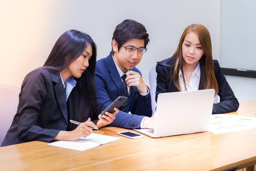 Asian business people make a group discussion in meeting room with document and computer putting on wooden table