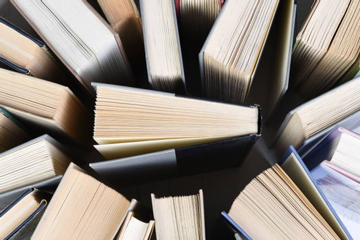Overhead view of a large group of used books in randomly arranged.