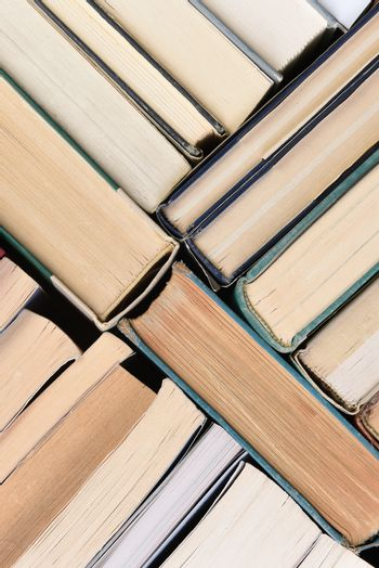 A large group of used books in random order seen from directly above, vertical format.