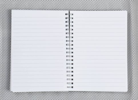 High angle shot of an open notebook on a silver mesh background.