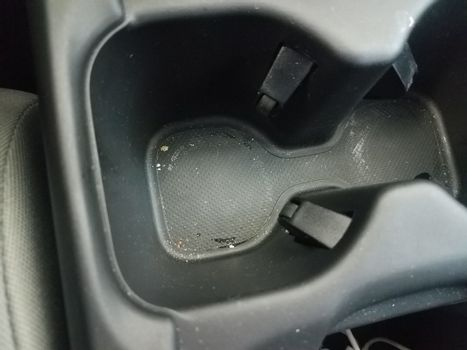 black plastic cupholder in car with dirt or grime