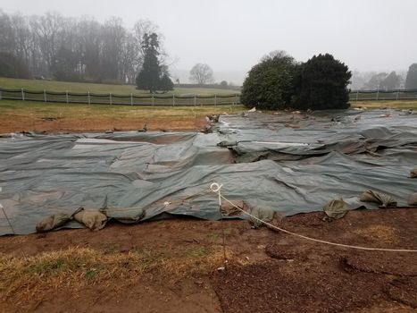 plastic tarp on wet ground with sandbags at dig site