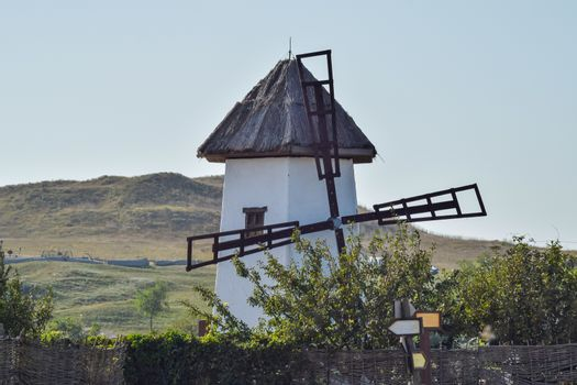 Old stone mill with a thatched roof. Mill on the background hills.