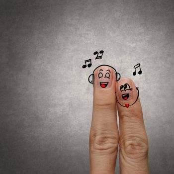 A happy finger couple in love with painted smiley and sing a song