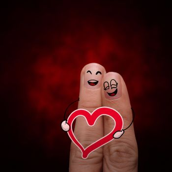 A happy finger couple in love with painted smiley and hold heart