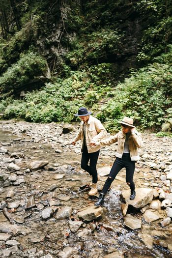 Young couple at the Carpathian - Happy tourists visiting mountains. Lovestory. Tourists in hats. Military fashion