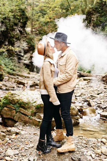 Couple in vape cloud. Two in smoke. Tourists in cold autumn forest with vape. Man and women in smoke. Two smokers. Beautiful couple in fog. E-cigarettes and people