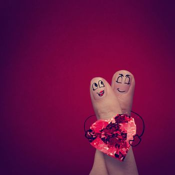 the happy finger couple in love with painted smiley and hold diamond ring heart shape