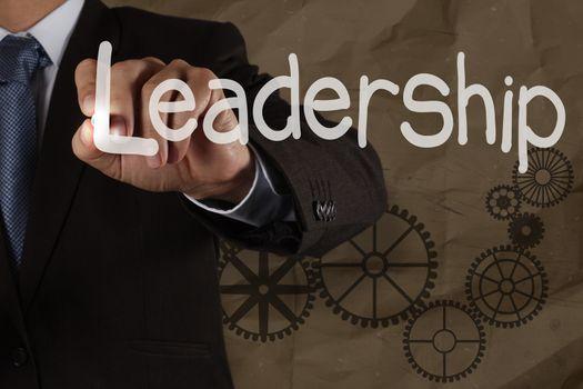 businessman writing leadership skill with gear on crumpled recyc