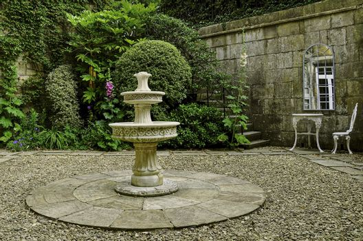 A stone walled cottage garden a central three tiered stone water feature and steps, shrubs and hollyhocks. The wall is decorated with a Georgian mirror infront of an ornate white wrought iron table and chair set of garden furniture.