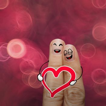 the happy finger couple in love with painted smiley and hold heart on nature background
