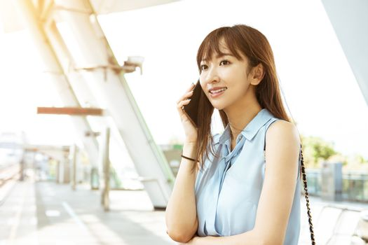 young business woman talking on the phone in  train station