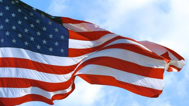 American Flag blowing in the wind with a blue sky background. USA American Flag. Waving United states of America famous flag in front of blue sky. Independence Day. Elections Day