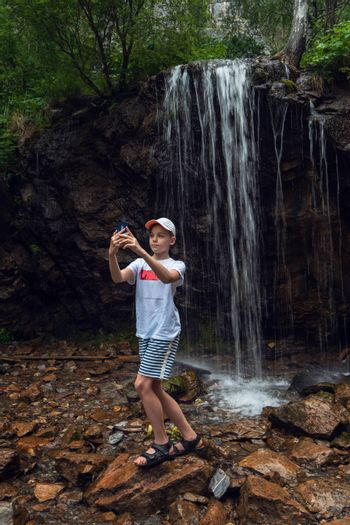 Stunning view of a boy tourist taking selfie photos with a smartphone at the waterfalls background in the Altai mountains.