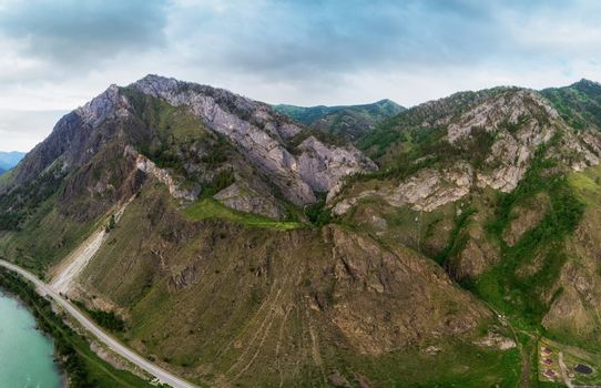 Beauty day in the mountains in Altay. Road, river and mountains. Aerial shot on drone