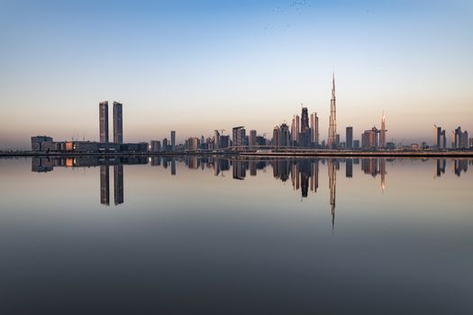 Scenic view of Dubai skyline early morning just after sunrise with skyscrapers mirroring in the water canal. United Arab Emirates (UAE), Middle East