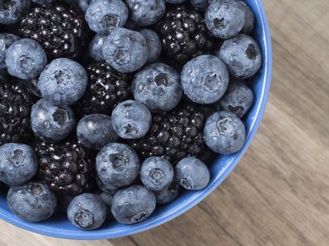 Forest berries (blueberry,bramble) in a ceramic blue  bowl. Top