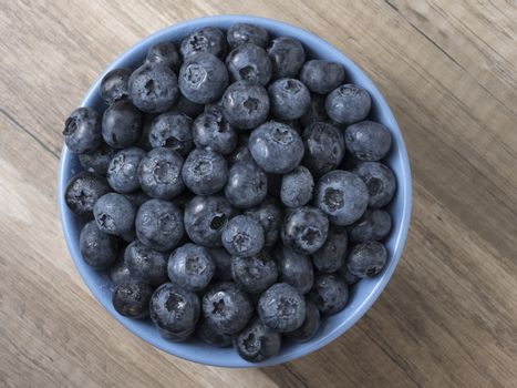 Bowl full of fresh ripe blueberries on a wooden background.