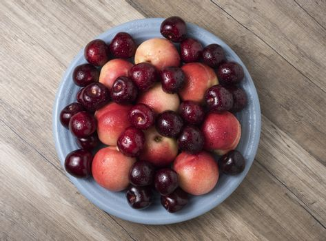 Sweet cherries and ripe juicy nectarines in a dish, on wooden ba