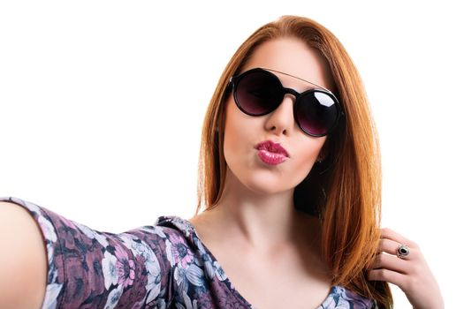 Young beautiful girl with sunglasses taking a selfie while blowing a kiss, looking at the camera POV, isolated on white background. Attractive redhead girl with long hair taking a selfie. Lifestyle, happiness, and social concept.