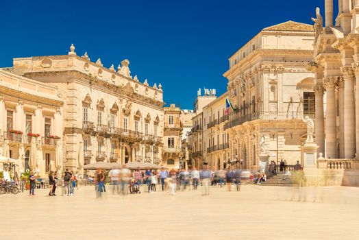 View of The Central Square in Ortygia (Ortigia, Piazza Duomo) with walking people. Historical buildings in the famous Sicilian town Syracuse (Siracusa), Italy