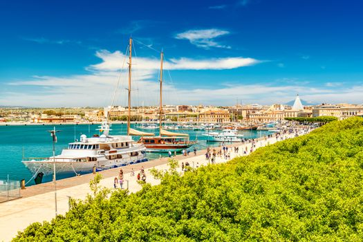 Beautiful view of the harbor in Syracuse with people walking along the promenade. Cityscape of Ortygia Island, Sicily, Italy